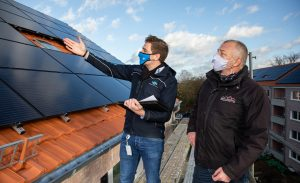 Bevor das Baugerüst entfernt wird, schauten sich Frederik Stroetmann (Stadtwerke Münster) und Andreas Jenschke (Wohn + Stadtbau) die neuen Photovoltaik-Anlagen an der Von-Stauffenberg-Straße noch einmal aus der Nähe an.
