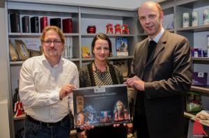Fotograf Martin Lohoff und Designerin Sabine Thiel überreichen das erste Exemplar ihres Kalenders an Dompropst Kurt Schulte (re.) (Foto: th)