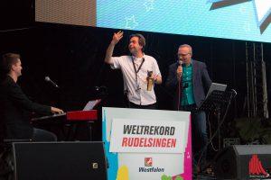 Jovel-Chef Marvin Lindenberg (Mitte) dirigiert die Rudelsinger und den Pianisten beim Weltrekordversuch. Rechts im Bild: Rudelsingen-Erfinder David Rauterberg. (Foto: cb)