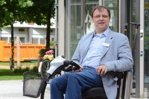 Dr. Theo van Gelder rollt als Seelsorger mit seinem E-Mobil über die Flure des Franziskus-Hospitals. (Foto: Bischöfliche Pressestelle / Ladermann)