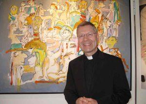 Weihbischof Dr. Stefan Zekorn vor dem Bild Menschenfamilie. (Foto: Jürgen Flatken)