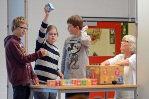 Eine Schülerin und zwei Schüler präsentieren ihren Mitschülern die 17 UN-Nachhaltigkeitsziele, an denen sich die Schule orientiert. (Foto: Bischöfliche Pressestelle/Ann-Christin Ladermann)