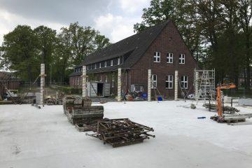 Blick auf die Baustelle der neuen Kita: Das Bestandsgebäude (Hintergrund) wird entkernt. Beim Anbau (Vordergrund) sind bereits die Bodenplatte und erste Stützen zu sehen. Foto: Wohn+Stadtbau.