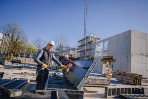 Bauarbeiter verteilen Abdichtungsmasse. Sie verhindert später das Eindringen von Grundwasser in die Bauteile. (Foto: Presseamt)