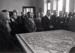 Stadtbaurat Peter Poelzig (weißer Schal) erläutert am 16. Januar 1941 unter anderem NSDAP-Gauleiter Alfred Meyer (li. mit Brille) die Pläne zur zukünftigen Gestaltung des NSDAP-Forums am Aasees. ( Foto: Stadt Münster, Sammlung Stadtarchiv)