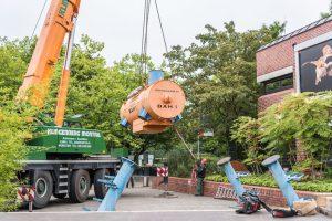 Mittels eines Krans wurde die Station vom Anhänger des LKWs zu den bereits platzierten Füßen der Station geschwenkt. (Foto: LWL / Steinweg)