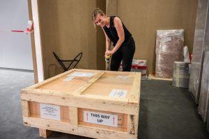 Ausstellungsmacherin Dr. Michaela Klösener freut sich über das erste, eingetroffene Ausstellungsobjekt und öffnet gespannt die Transportkiste. (Foto: LWL/ Heimann)