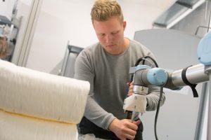 Moritz Wesseler stattet den Roboterarm mit einem Extruder aus. (Foto: FH Münster/Pressestelle)