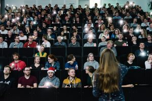 """Wie sie Informationen über DNA aus Bakterien liest, demonstrierte Dr. Julia Schnetzer anhand des Publikums: Die Besucher sollten per Handylicht ein Zeichen geben, ob sie die gestellte Frage mit """"Ja"""" beantworten, zum Beispiel: Hast du braune Augen? (Foto: FH Münster/Maxi Krähling)"""