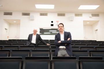 """Allein im Hörsaal, der eigentlich bis auf den letzten Platz gefüllt wäre: das Moderatorenduo der """"Ausgezeichnet."""" Prof. Dr. Richard Korff (l.) und Carsten Schröder. (Foto: FH Münster/Katharina Kipp)"""
