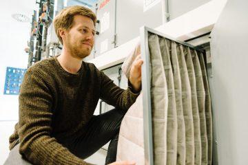 EPA-Filter sind besonders feine Taschenfilter, die selbst feine Aerosole filtern können. Der wissenschaftliche Mitarbeiter Steffen Jacobs baut hier einen neuen Filter in eine Klimaanlage ein. (Foto: FH Münster/Maxi Krähling)