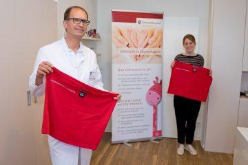 Chefarzt Dr. Rüdiger Langenberg (l.) und Sabrina Schulz vom Fundraising mit zwei Exemplaren der neuen Bonding-Tops des Clemenshospitals. (Foto: Alexianer Misericordia GmbH)