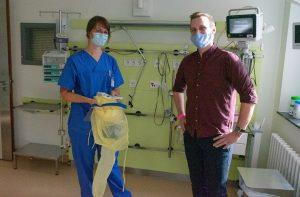 Carla Mefus (l.) zeigt Florian Janssen die Schutzkleidung, die alle Mitarbeiter der Intensivstation tragen müssen, wenn sie das Zimmer eines Corona-Patienten betreten. (Foto: Clemenshospital / Michael Bührke)