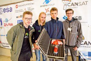 """Das Team """"CamSat"""" (v.l.): Ruben Förster, Pepe Berges, Luca Sapion und Marvin Langenberger mit ihrem Satelliten nach dem erfolgreichen Flug (Foto: Bührke)"""