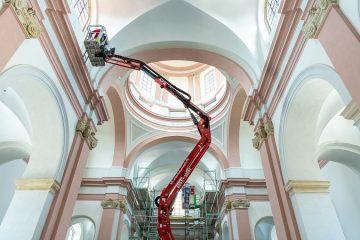 Per Hubsteiger bringen Handwerker Akustikelemente hoch oben an den Wänden der Dominikanerkirche an. Voraussichtlich im Sommer kann nach allen Umbau- und Sanierungsarbeiten die profanierte Kirche als Konzert- und Veranstaltungssaal wiedereröffnet werden. (Foto: Stadt Münster / Michael C. Möller)