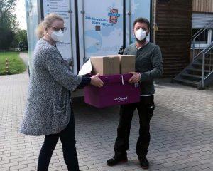 Eine Sozialarbeiterin und der Hausmeister einer Geflüchtetenunterkunft nehmen den Impfstoff entgegen. (Foto: Sozialamt Münster)