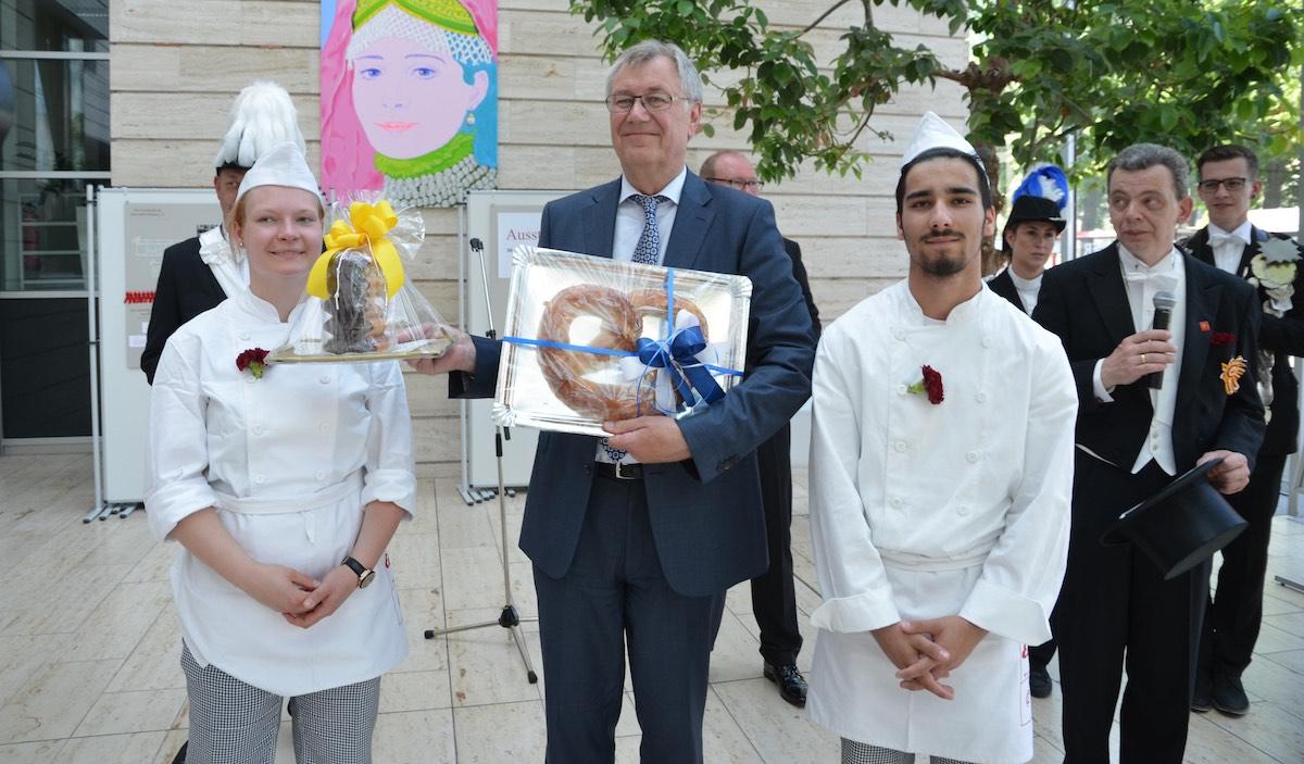Regierungspräsident Prof. Dr. Reinhard Klenke (Mitte) freut sich über Baumkuchen und Brezel der Bäckergilde und Konditoren-Innung Münsterland. (Foto: RP)