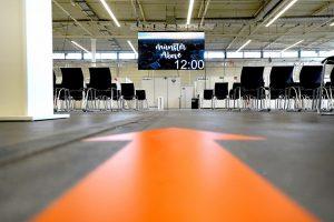 Im Wartebereich des Impfzentrums Münster – hier werden die geimpften Personen noch für etwa eine halbe Stunde verbleiben – gibt es ein kostenfreies WLAN-Angebot und eine LED-Wand mit Luftaufnahmen von Münster 4 Life.