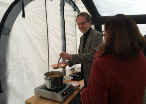 Udo Schröder-Hörster (JUH) reicht die vorbereitete Kartoffelsuppe. (Foto: JUH)