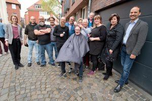 Für das Foto ausnahmsweise auf der Straße vor dem Treffpunkt, normalerweise in dessen geschützten Räumen: Münsters Friseure schneiden Menschen in sozialen Notlagen kostenlos die Haare. (Foto: Pressefoto)