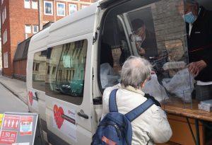 Helfer verteilen vor dem Borromaeum warme Mahlzeiten an Bedürftige. (Foto: Malteser Münster / Hölschermann)