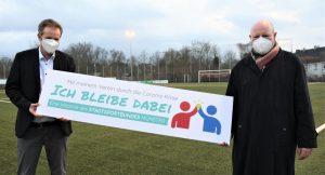"""""""Ich bleibe dabei"""" und """"Stay in your Club"""" heißt es auf zwei Logos, mit denen die Mitglieder des Stadtsportbundes im Rahmen einer Kampagne zum Verbleib in und zur Solidarität mit ihren Sportvereinen aufgerufen werden. Gemeinsam mit SSB-Chef Michael Schmitz (li.) solidarisierte sich auch OB Lewe. (Foto: SSB)"""