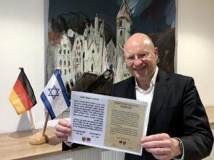 Oberbürgermeister Markus Lewe präsentiert die Urkunde, mit der die Partnerschaft zwischen Rishon LeZion und Münster vor genau 40 Jahren besiegelt wurde. (Foto: Stadt Münster)