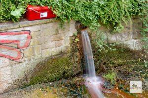 Direkt neben dem Rohr mit dem abgepumpten Grundwasser steht die geheimnisvolle rote Kiste. (Foto: Michael Bührke)