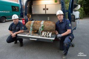 Peter Asmussen (li.) und Horst Schöwe vom Kampfmittelbeseitigungsdienst der Bezirksregierung mit der entschärften Bombe auf dem Gelände der Pötterhoek-Schule. (Foto: Thomas Hölscher)