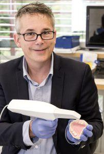 Dentallabor-Geschäftsführer Karsten Tegtmeyer mit dem Mundscanner, der Teil der volldigitalen Kronen-Herstellung ist. (Foto: UKM)