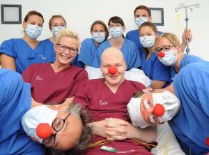 Für ein paar Minuten vergessen, dass man auf der Isolierstation gefangen ist: Louis und seine Mutter Nicola freuen sich über den Besuch der UKM Clinic-Clowns. Pflegerin Lea Preiss (r.) machte die regelmäßigen Visiten der Clowns erst möglich. (Foto: UKM)