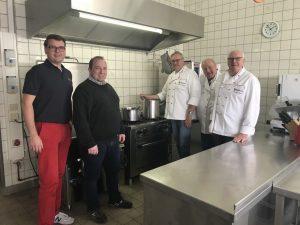 (v.l.): Tobias Jainta (Stadtbeauftragter), Kai Flottmann (Geschäftsführer) und das Küchenteam rund um Bernhard Kuper (v.r.) freuen sich auf den Einsatz. (Foto: Malteser)
