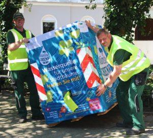 Fabian Böckmann und Bernd Lohmann vom Amt für Grünflächen, Umwelt und Nachhaltigkeit stellen im Hansaviertel einen der 37 Wassercontainer auf. (Foto: Stadt Münster)