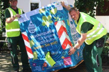 Foto: Fabian Böckmann (l.) und Bernd Lohmann vom Amt für Grünflächen, Umwelt und Nachhaltigkeit stellen im Hansaviertel an der Meppener Straße/Ecke Papenburger Straße einen der 37 Wassercontainer auf. (Foto: Stadt Münster)