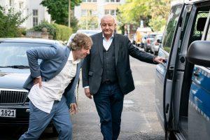 Ekki (Oliver Korittke, l.) zog sich leichte Blessuren zu, während Wilsberg (Leonard Lansink, r.) einen Polizeiwagen organisiert hat, als wäre es ein Taxi. (Foto: ZDF / Thomas Kost)