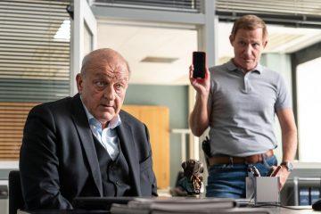 Overbeck (Roland Jankowsky, r.) fragt nach dem Handy, das Wilsberg (Leonard Lansink, l.) entwendet hat. Wilsberg erklärt, dass es sich dabei um ein beschlagnahmtes Objekt vom Finanzamt Münster handelt.