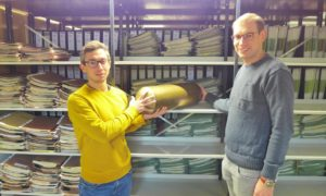 Die Archivare Michael Jerusalem (l.) und Max Pfeiffer suchen einen geeigneten Platz im Magazin des Stadtarchivs für die Zeitkapsel der Künstlergemeinschaft Schanze. Erst in 100 Jahren wird sie ihren Inhalt preisgeben. (Foto: Stadt Münster)