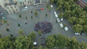 Flashmob auf dem Domplatz. Die kleine Gruppe links stellt die Menge der nach Deutschland Geflüchteten im letzten Jahr dar, die große Menge rechts die deutsche Bevölkerung. (Foto: Drones Photography / David Schnitker)