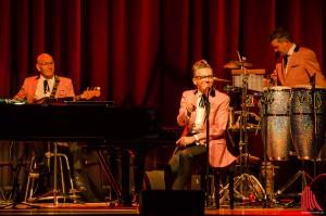 Beim Erzählen seiner haarsträubenden Geschichten nahm Götz Alsmann auch schon mal die Finger von den Tasten. Im Hintergrund: Michael Müller (Bass) und Markus Paßlick (Percussion). (Foto: th)