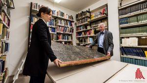 Dr. Annik Wüthrich und Prof. Dr. Erhart Graefe müssen das große Buch zu zweit tragen. (Foto: wf / Weber)