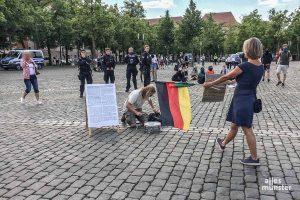 """Die """"Hygiene-Demos"""" auf dem Domplatz (hier eine Teilnehmerin mit einer Deutschlandfahne) rufen auch regelmäßig Gegendemonstranten auf den Plan. (Archivbild: Philipp Schröder)"""