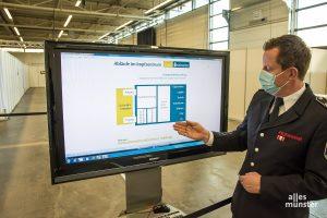 Jörg Rosenkranz von der Feuerwehr Münster erläutert die Abläufe im Impfzentrum. (Foto: Thomas Hölscher)
