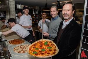 Klaus Rader (r.) und Friedemann Finteis (2.v.r.) präsentierten bei der Eröffnung der 41. L'Osteria Filiale in Münster persönlich die leckeren und 45 Zentimeter großen Pizzen. (Foto: th)