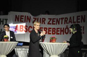 Beim Neujahrsempfang der Grünen protestierten Aktivisten gegen die Einrichtung einer ZAB in Münster und entrollten Transparente. Mit im Bild sind die Grünen-Politikerinnen Josefine Paul (li.) und Maria Klein-Schmeink (Bildmitte). (Foto: No ZAB)