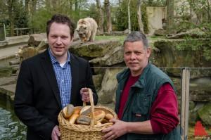 Jan Schönberg von Wellhausen & Marquardt Medien (li.) und Revierleiter Peter Vollbracht mit Patenbärin Leila im Hintergrund, die bereits an einem Brötchen knabbert. (Foto: th)